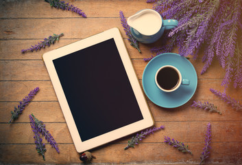 cup of coffee, tablet and milk jar, bunch of lavender on the wonderful brown wooden background