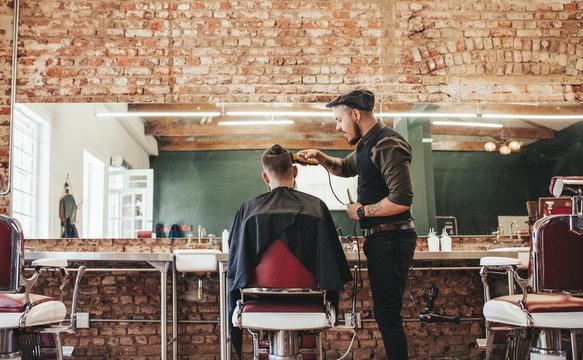 Hairstylist cutting hair of male customer