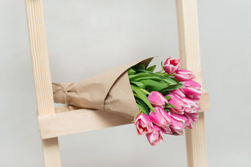 Beautiful bouquet of tulips on wooden stairs  on the light gray background.