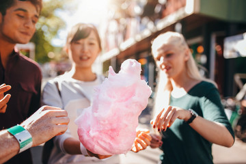 Three young people sharing cotton candyfloss