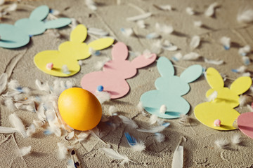 Yellow egg and Garland with colorful paper rabbits and feathers on concrete background. Concept Easter. Top view.