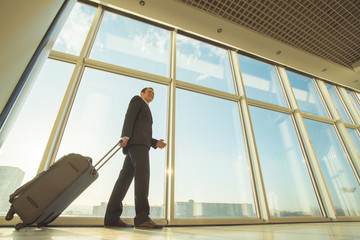 The businessman walk with a suitcase near panoramic windows