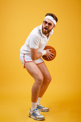Vertical image of concentrated sportsman in sunglasses playing basketball