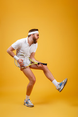 Vertical image of bearded sportsman playing on tennis racquet
