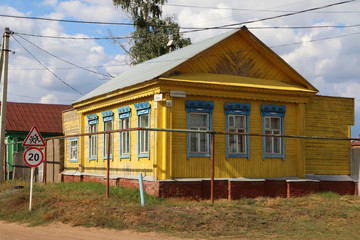 Wall Mural - Old traditional wooden house in the Russian village against a blue cloudy sky