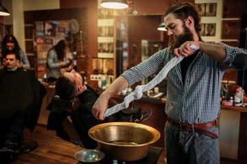 Barber squeeze towel in copper basin at barbershop