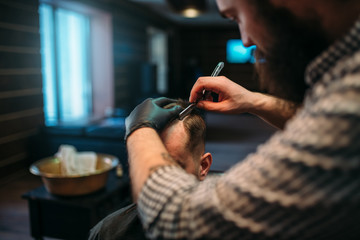 Barber shaves the hair by straight razor