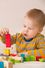 Cute little toddler playing with colorful wooden bricks on the white table at home. boy building tower with geometric shapes. Learning and education concept.