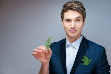beautiful young attractive man in a blue business suit and white shirt in a studio with green fennel in hand and in your pocket