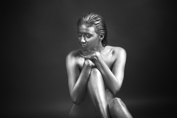 Beautiful woman painted with silver paint on dark background