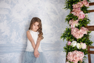 Photo of a cute little girl in a blue dress in a studio