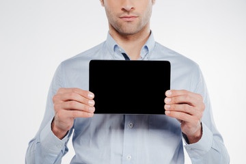 Cropped image of man showing blank tablet computer screen
