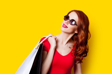 beautiful young woman with shopping bags  on the wonderful yellow background