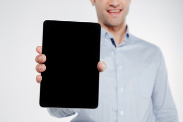 Cropped image of smiling man showing blank tablet computer screen