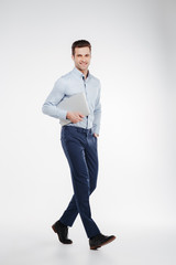 Vertical image of smiling business man walking with laptop