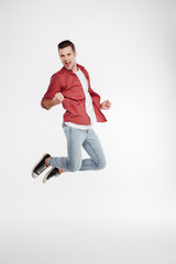 Vertical image of happy man jumping in studio