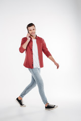 Vertical image of happy man walking and talking on phone
