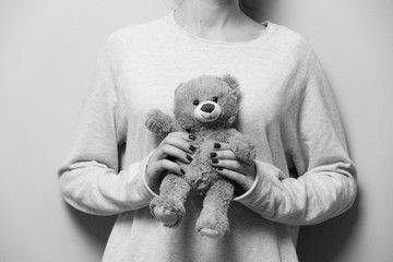 beautiful young woman hands holding a cute teddy bear white and black