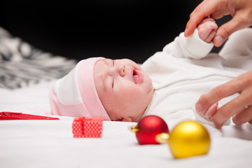 male hands touching cute crying baby near gifts and baubles on the white blanket