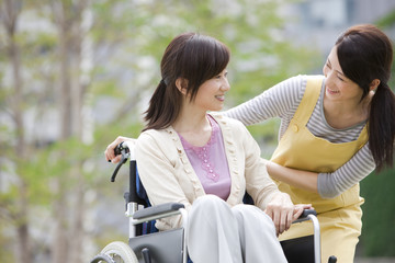 Caretaker and mature woman on wheelchair talking