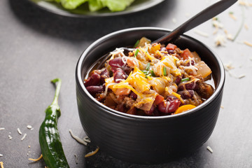 Kidney Bean Chili with tomato chunks and onion topped with cheese in large black bowl horizontal shot