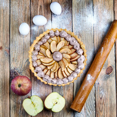 Beautiful classic apple tart with meringue. American / French pie with apples and whipped egg whites. Chocolate meringue on the cake. Baking from short pastry. Kitchen table in flour.