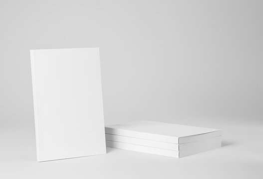 Real paperback white book next to a stack of books on a gray background