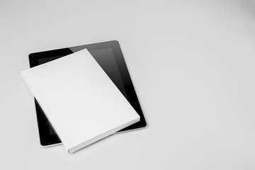 Real paperback white book over a tablet on a gray background