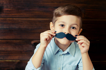 A kid with props for a photo booth. A child with the requisite mustache on wooden background.