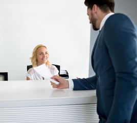receptionist attending handsome passenger