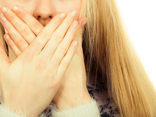 Shocked young woman covering mouth with hand