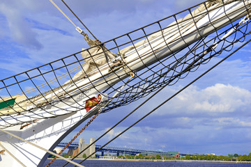 Nautical maritime scene with ropes and mast on a ship on a dock by the water