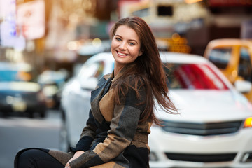 Beautiful young adult woman with natural cute teeth smile looking at camera and enjoy healthy life in the city.