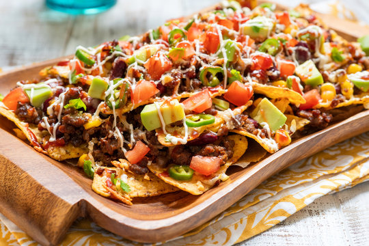 Nacho corn tortilla chips with cheese, meat, guacamole and red hot spicy salsa