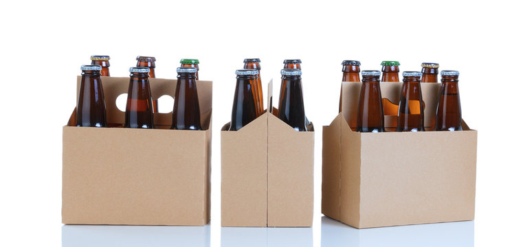 Six packs of glass bottled beer in generic brown cardboard carriers on white background