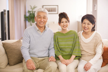 Portrait of family sitting on sofa, smiling
