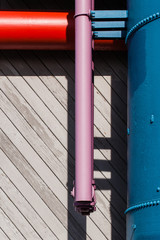 Colorful pipes making right angles in front of a wooden slat