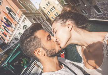 Young couple taking a selfie while kissing in Venice