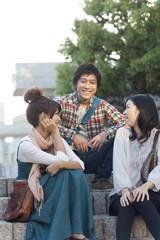 Three university students talking at staircase
