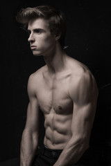 Young Handsome man with great fit body posing at the chair