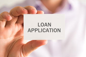 Businessman holding a card with LOAN APPLICATION message