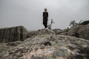 Artistic photo of a blond girl in a transparent black dress walking on the rocks in the field a cloudy day. The aesthetic is sinister and a little dark.