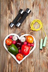 Sport and diet. Vegetables  dumbbells. Peppers, tomatoes, garlic, onions,  radishes in the heart on rustic background