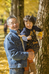 Portrait of grandfather and granddaughter in autumn