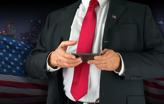 Closeup of a United States of America politician with red neck tie and American flag lapel pin texting on his cell phone.