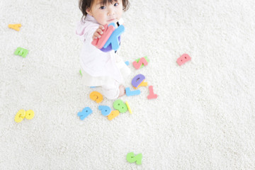 Baby girl holding alphabet and number toys
