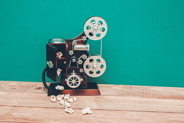 vintage music box in the shape of an old movie camera  and popcorn. retro tones. copy space