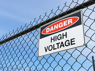 Danger, High Voltage sign on fence with blue sky background