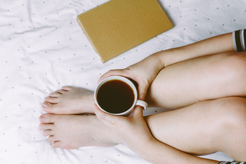 Woman on the bed with cup of coffee