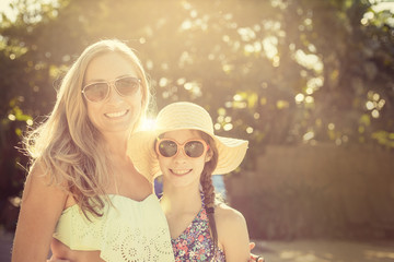 Two smiling girls, a mother and a daughter, enjoying a warm summer day together outside. Lots of copy space. Ray of sunshine shinning through. Bright vibrant happy photo